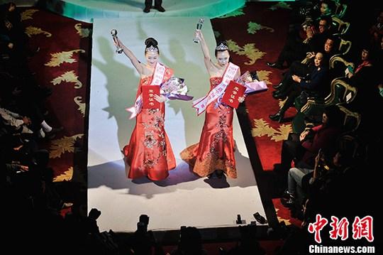 11月17日,两名冠军选手向T台下的观众招手示意。中新社发 佟郁 摄