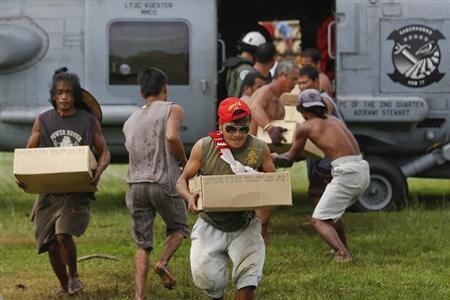 菲律宾难民从美国军用直升机上搬下救援物资。