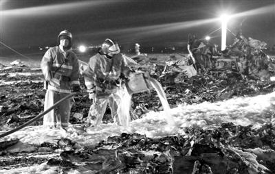 11月17日,俄罗斯喀山机场,消防人员在客机失事现场进行清理工作。