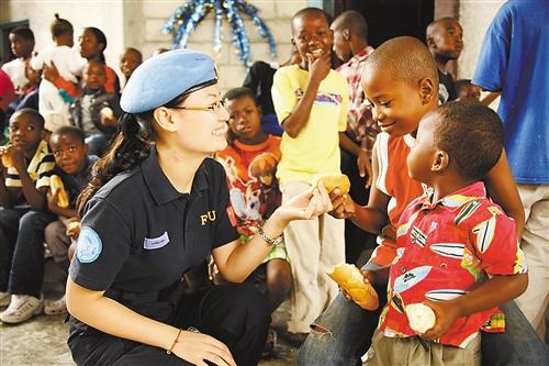 重庆 杨彬与/杨彬与海地当地儿童在一起。重庆市公安边防总队供图
