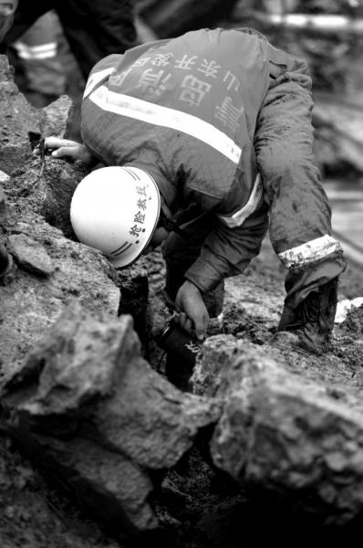 24日,一位消防官兵在青岛开发区斋堂岛街路段仔细搜寻事故遇难者。