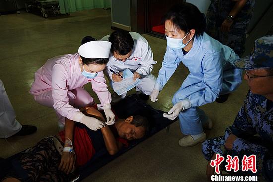 """首批因""""海燕""""强台风袭击受伤的3名菲律宾患者通过菲海军巡逻艇被转送到中国海军和平方舟医院船,海上医院第一时间组织医务人员为上着实施了手术治疗。"""