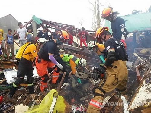 """24日,被派往遭受强台风""""海燕""""袭击的菲律宾的韩国海外紧急救援队在本次台风的重灾区塔克洛班市进行搜救活动。(韩联社)"""