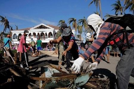 """当地时间25日,台风""""海燕""""肆虐后的菲律宾塔克洛班,幸存者和志愿者开始进行大规模灾后清理。"""