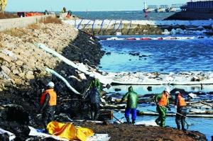 11月27日,在黄岛油港码头附近,工人在清理围堵在入海口内的油污。新华社发