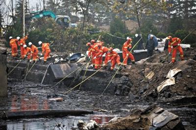 消防员在发现遗体的出事现场周边搜寻是否还有遗体。