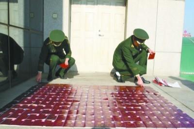 """11月22日,辽宁边防总队侦查队办案人员在清理""""6·27""""特大组织偷越国境案部分护照。孙模同 摄"""