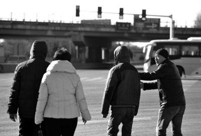 """""""窦老爹""""和孩子们过马路,紧张地招呼大家。"""