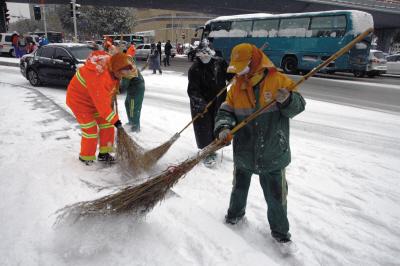 冰雪路面给环卫工人除雪带来困难。