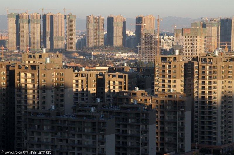 """2013年11月22日,昆明呈贡,是中国比较有代表性的""""鬼城""""之一。尽管房屋空置率极高,呈贡的施工仍在继续,楼盘像大树一天天地长高。吴长青/CFP"""