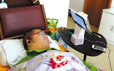 """11月14日,29岁的脑瘫患者汤仪躺在床上,用嘴巴叼着自制的""""触摸棍""""上网。今年7月,他开起自己的网店,用挣来的钱孝敬父母,并帮助更多有需要的人。"""
