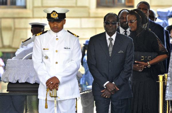 12月11日,在南非比勒陀利亚,津巴布韦总统穆加贝前右瞻仰曼德拉遗容。 新华社/美联