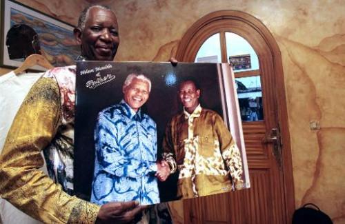 图为专为曼德拉打理衬衫的裁缝师魏陶哥(Pathe Ouedraogo)手中拿着一幅他与曼德拉握手的合影。