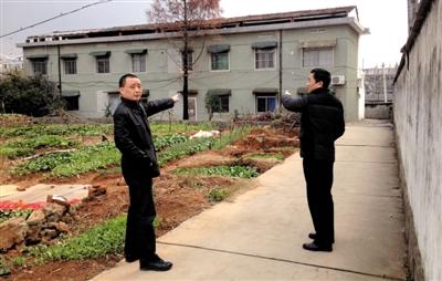 12月18日,被停职半月的陈龙(左)指着自己家所在的两层建筑。新京报记者 刘刚 摄