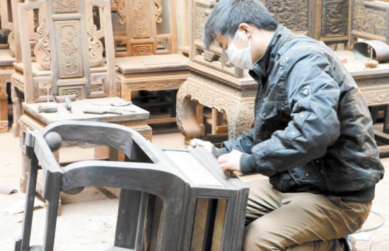 18日,市嘉华仿古工艺木业厂生产车间,员工正在精心打磨紫光檀家具.