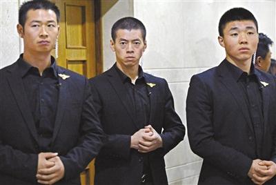 丁琨(中)和另外两名保镖在门口守候,他们的视线要不留死角。