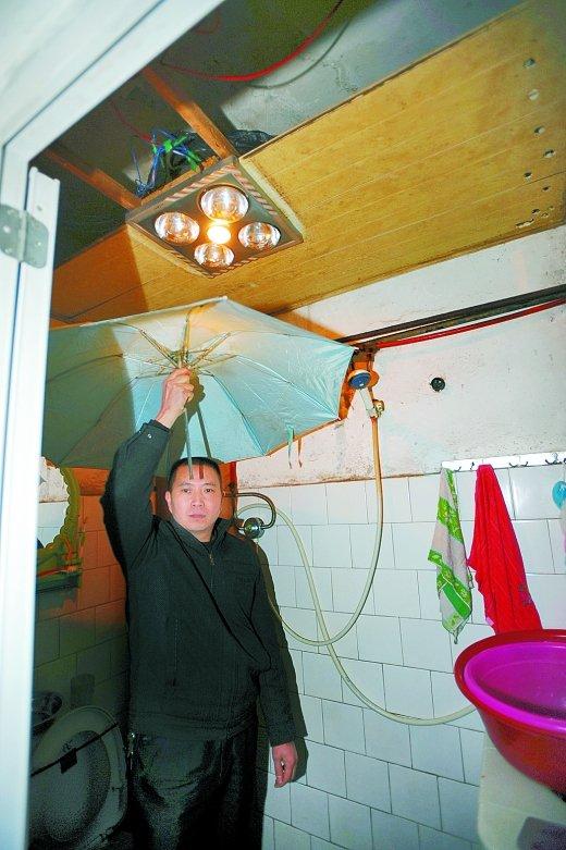 厨房天花板漏水,陈兴宇只能打着雨伞做饭。