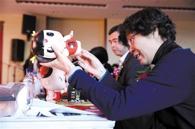 11月27日,邮储银行创富大赛南部赛区决赛,评委查看参赛企业带来的招财童子动漫玩偶。新京报记者 李冬 摄