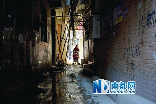 一女子推着婴儿车行经事发路段。脚手架下方的巷子不时有沙石坠落。南都记者 梁炜培 摄