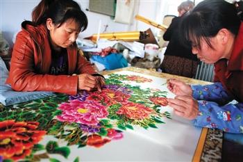 牡丹图的剪纸套上一层金箔剪纸层,用的也是套层套色的办法