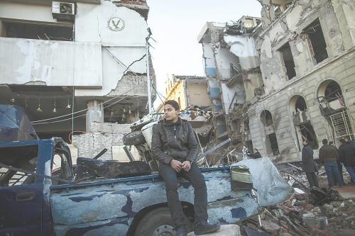 埃及曼苏拉市警察局24日遭汽车炸弹袭击,被疑是穆兄会的报复。图为一名男子在被炸毁的警察局前。