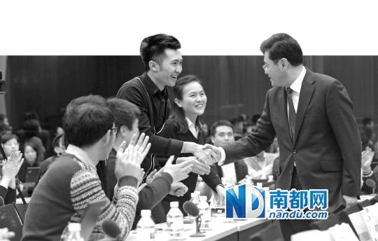 12月25日,外交部发言人秦刚(右一)与活动参与者握手交谈。