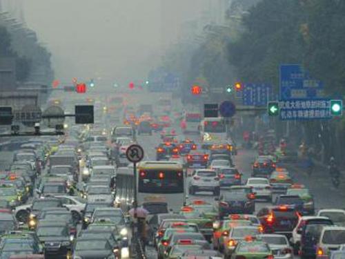 2013年12月的一天,雾霾天气中,车辆开着车灯缓慢同行。(华西都市报资料照片)