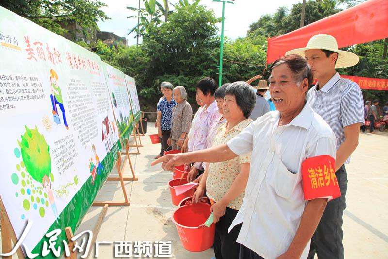 村民现场观看清洁乡村板报-南宁青秀区 南阳经验 建设美丽幸福村坡
