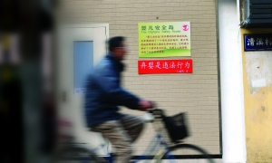"""""""弃婴岛""""的大门上贴上了红底白色的提醒标语:弃婴是违法行为 现代快报记者 赵杰 摄"""