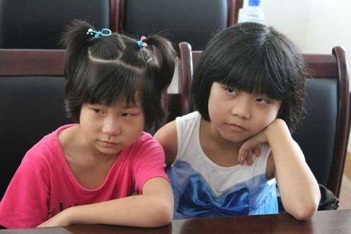 """7月24日,中国石化""""健康快车""""龙岩回访,去年做过白 内 障手术的小女孩妍妍(左一)重见光明,她看到屏幕中的自己时哭了。(张梅/摄)"""
