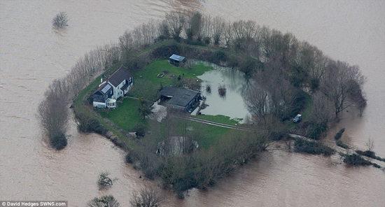 """夫妻二人携手共建拦洪坝,阻挡洪水房屋变""""孤岛""""。"""