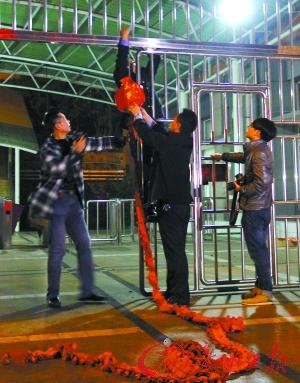 23时50分 整个火车站关门之前,工作人员在出口处准备燃放鞭炮纪念这不平凡的日子。