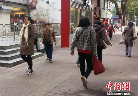 冷空气袭击广东,广州市民戴围巾御寒。 奚婉婷 摄
