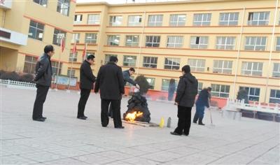 """1月3日下午5时许,五台县实验小学校园内,一名教职工将桶装机油淋在用木炭垒起的""""旺火""""堆上,为其助燃。"""