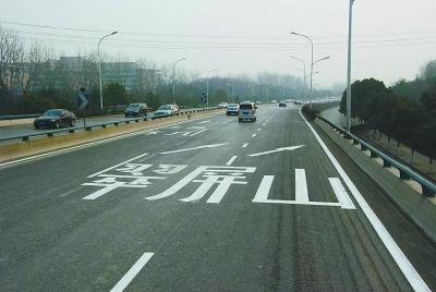 机场高速主线入口处,交警重新漆画路面标识。 本报记者 王茸摄