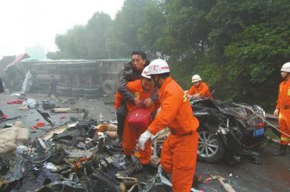 汽车交通 汽车交通新闻  车祸现场,两村民正在捡拾散落的饮料.