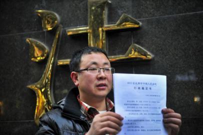 """彭州乌木案就是""""民告官"""",2013年1月16日,原告吴高亮出示法院公布的行政鉴定书。(本报资料图片)"""