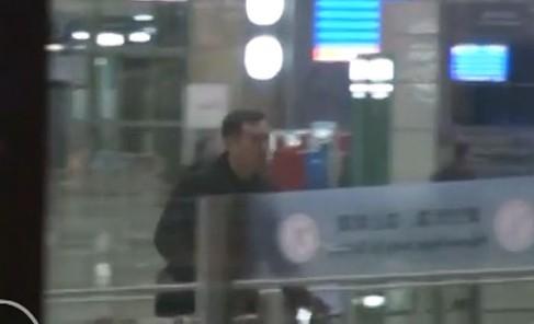 他独自拉着行李箱坐电梯上到机场出发大厅,然后走出大厅到达通道等车。