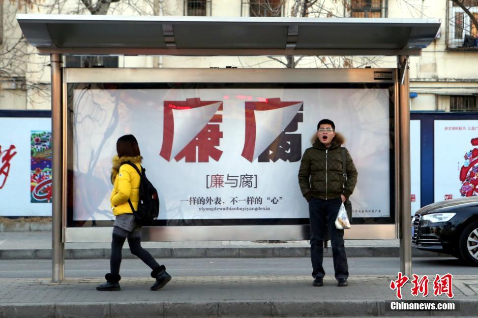 1月15日,市民在北京甘家口一公交站候车,身后的反腐倡廉公益广告格外图片