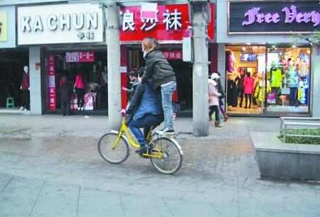 街头杂耍 女生站在自行车后座,男生往前骑行,这样的街头杂耍非常危险.