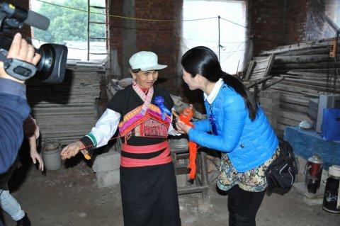 为表感谢花腰傣族阿玛拿出了象征吉祥如意的红头绳给慰问代表系上祝福