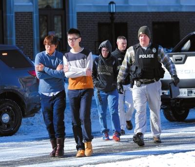 1月21日,警察护送学生离开发生枪击事件的教学楼。新华社/美联