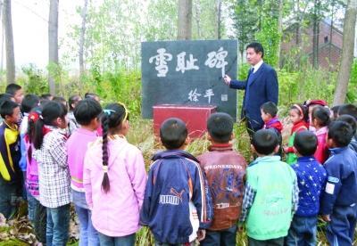 """徐振理在""""雪耻碑""""前向小学生们讲述当年的那段抗战历史。"""