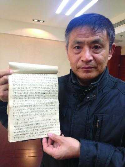 徐振理向记者展示这部手写的《家史》。