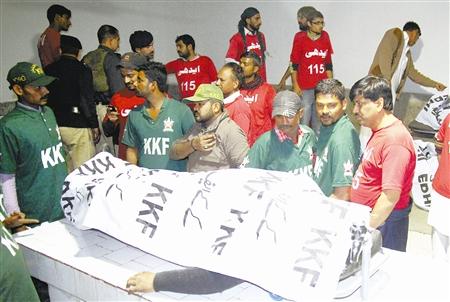 1月25日,在巴基斯坦卡拉奇市一家医院,人们围在死者遗体旁。据巴基斯坦媒体报道,巴南部港口城市卡拉奇25日夜晚发生两起恐怖袭击,造成至少6名警察死亡。