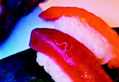 视频中一条白色寄生虫在鱼片上蠕动。美国《世界日报》援引视频截图