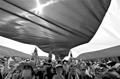 反政府示威者在一面巨大的泰国国旗下示威游行.-泰大选提前投票