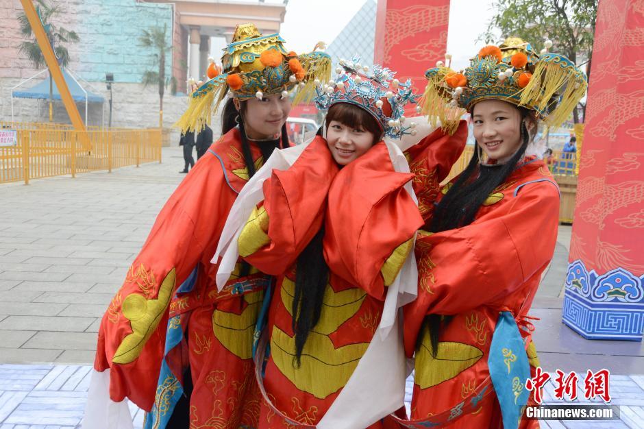 1月28日,三位美女财神正在游客面前耍萌。当日,在湖南长沙世界之窗举办的新春庙会上,三位身着财神服饰的女性工作人员受到了游客的热捧。