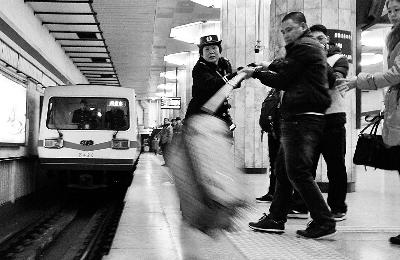 进站地铁紧急停车后,地铁工作人员用长竿将行李箱挑上来。