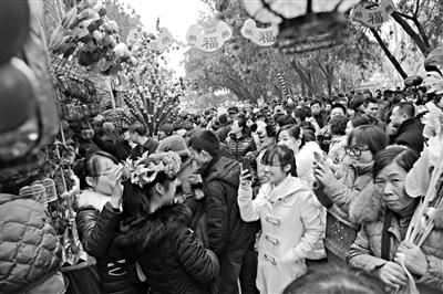 昨日,地坛庙会上,一女孩在人群中拍照。北京市假日办统计,昨日21个重点景区共接待游客27.5万人次,庙会和祈福场所游客最集中。新京报记者 秦斌 摄